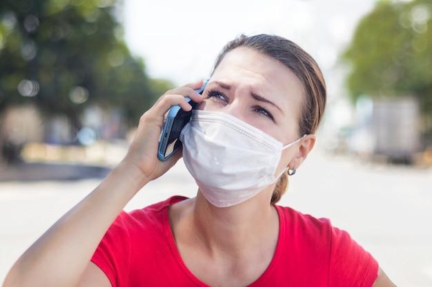 A menina, mulher ansiosa na máscara médica estéril protetora em seu rosto que chama a ambulância, precisa de ajuda, falando no telefone celular ao ar livre na rua asiática. vírus, conceito chinês de pandemia de coronavírus Foto Premium