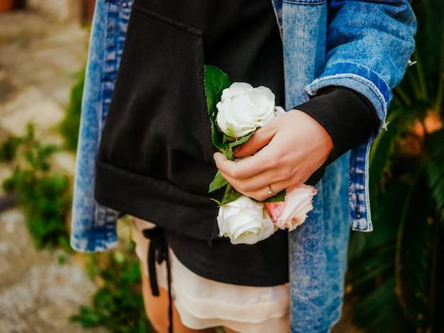 A menina na jaqueta ocasional das calças de brim e o hoodie preto que guardam um ramalhete das rosas brancas e cor-de-rosa florescem. foco seletivo. conceito de entrega de flores Foto Premium