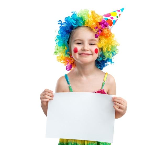 A menina na peruca do palhaço prende o papel em branco, isolado no fundo branco Foto Premium