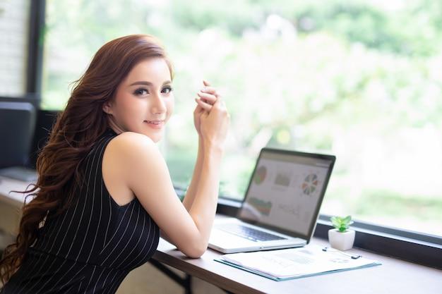 A menina nova asiática do negócio relaxa o trabalho com o portátil no café da cafetaria. Foto Premium