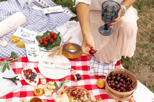 A menina prende cerejas maduras suculentas na mão no contexto de uma manta de piquenique quadriculada com comida espalhada nela Foto Premium