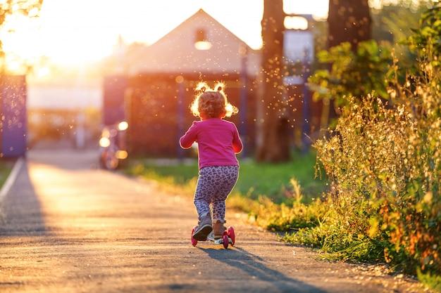 A menina que a criança monta no parque com a mãe a scooter Foto Premium