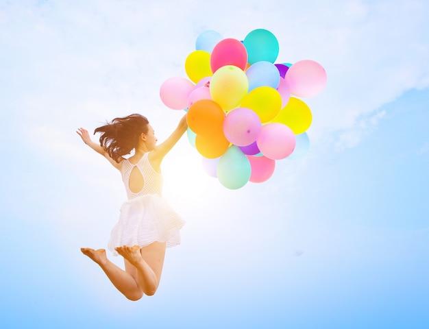A menina que salta com balões Foto gratuita