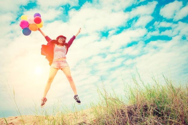 A menina que salta na praia com balões coloridos Foto gratuita