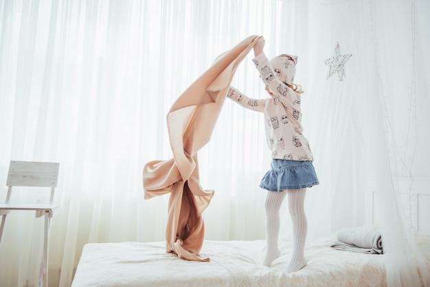 A menina quer enrolar um cobertor na luz do quarto Foto Premium