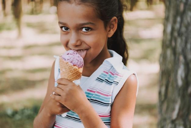 A menina satisfeita nova come o gelado na floresta. Foto Premium