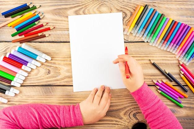 A menina se prepara para pintar em uma folha de papel em branco. Foto Premium