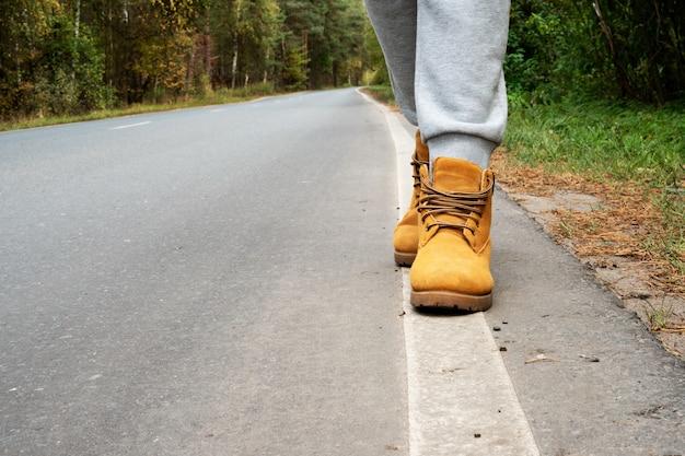 A menina segue a linha das marcações da estrada. caminhe pela estrada do outono. hipster viajando, estilo de vida. marcações de estrada brancas e pernas em sapatos de outono. Foto Premium