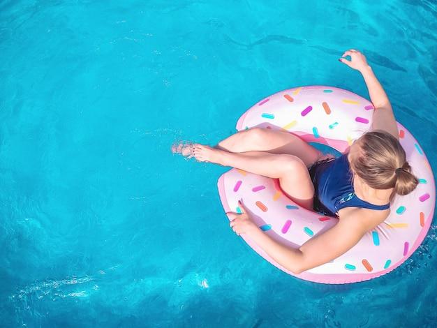 A menina senta-se em um anel de borracha em forma de um donut em uma piscina azul. hora de relaxar em um colchão de ar. copie o espaço. Foto Premium