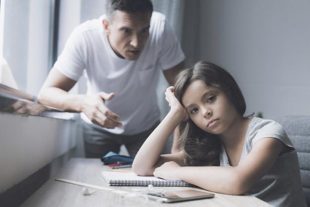 A menina senta-se na tabela quando o pai irritar Foto Premium