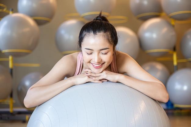 A menina sentada relaxa com a bola no ginásio. Foto gratuita