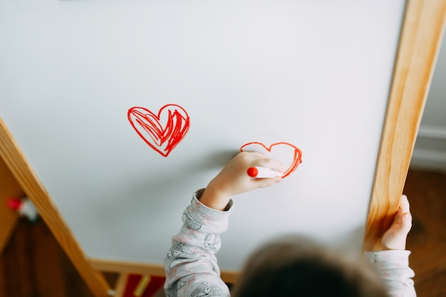 A menina tira o coração com marcador em um quadro-negro branco. dia das mães. dia dos namorados Foto Premium
