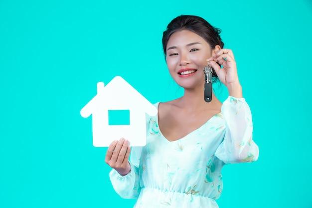 A menina usava uma camisa branca de mangas compridas com padrão floral, segurando o símbolo da casa e segurando um chaveiro com um azul. Foto gratuita