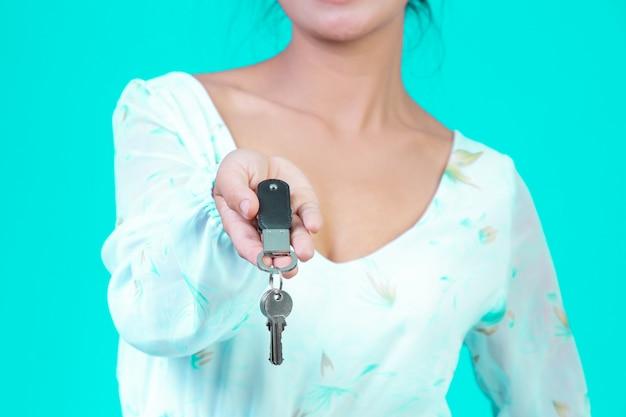 A menina usava uma camisa branca de mangas compridas com um padrão de flores segurando um chaveiro com um azul. Foto gratuita