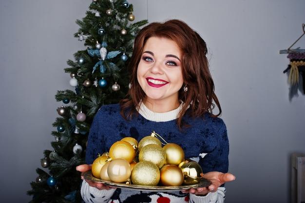 A menina veste a camisola quente com a árvore de natal no estúdio com as decorações de natal nas mãos. feliz conceito de férias de inverno. Foto Premium