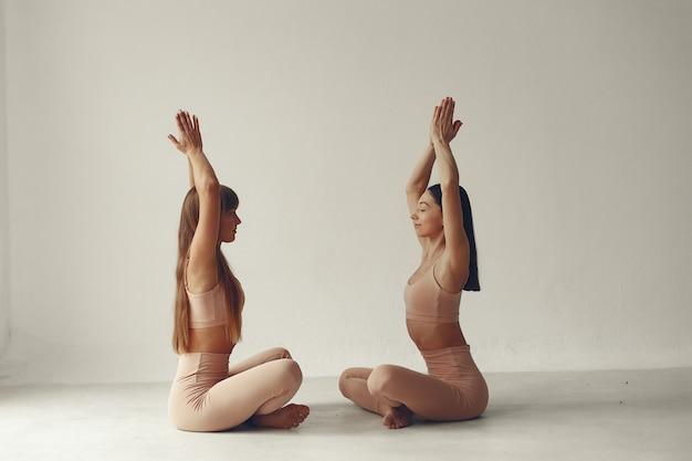 A meninas bonitas está envolvida em um estúdio de yoga Foto gratuita