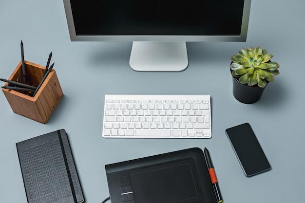 A mesa cinza com laptop, bloco de notas com uma folha em branco, vaso de flores, caneta e tablet para retoque Foto gratuita