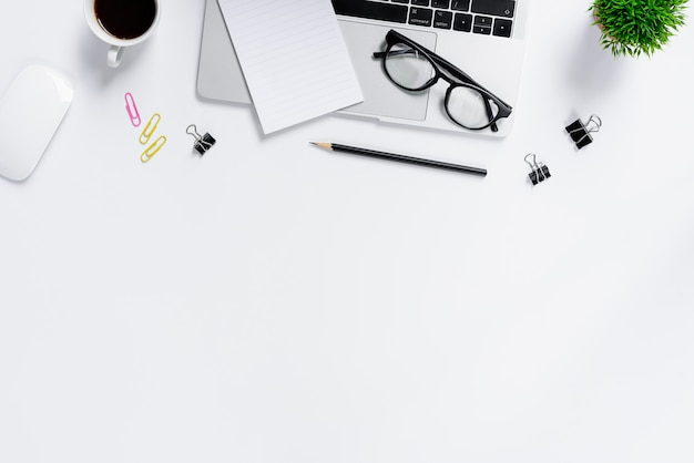 A mesa de escritório azul e equipamentos para trabalhar em vista superior e plana leigos no fundo branco Foto Premium