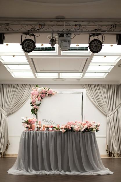 A mesa para os noivos é decorada com flores frescas no restaurante. iluminação e holofotes quadrados Foto Premium