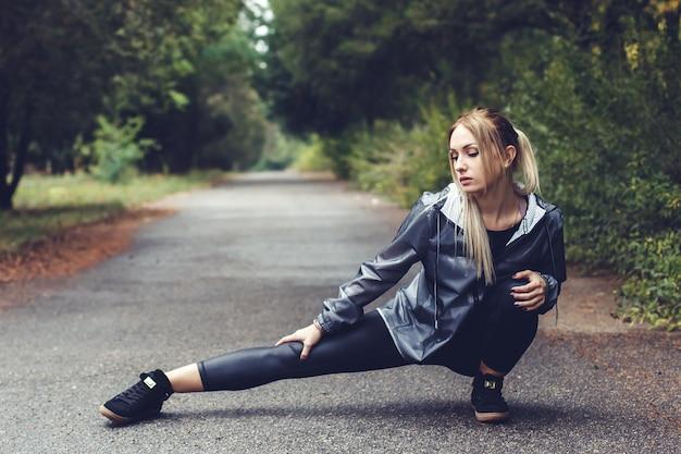 A moça atrativa que faz o esticão ostenta exercícios em um parque da cidade no tempo chuvoso. Foto Premium