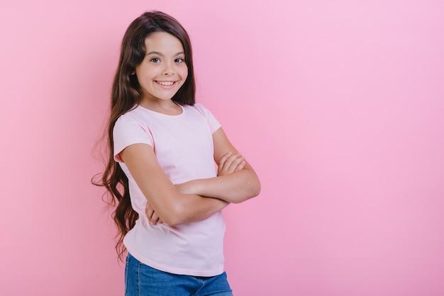 A moça de sorriso com mãos dobradas está vestindo no t-shirt que olha a câmera. Foto Premium