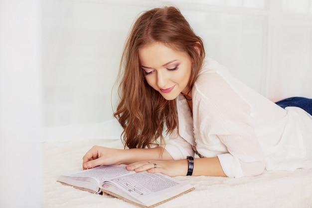 A moça encontra-se e lê-se o livro. o conceito de lazer Foto Premium