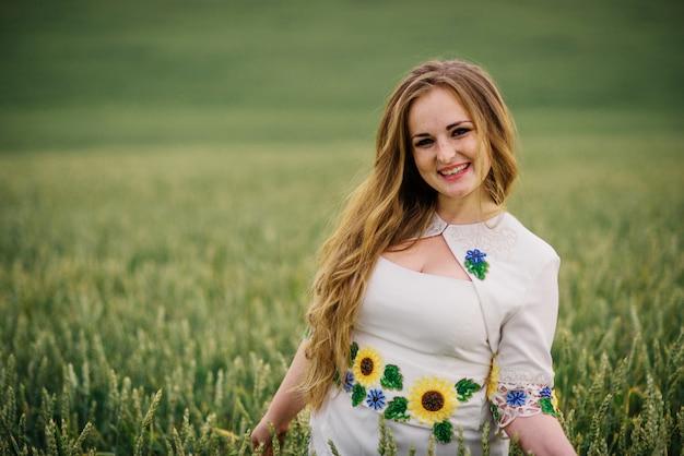 A moça no vestido nacional ucraniano levantou no campo da grinalda. Foto Premium