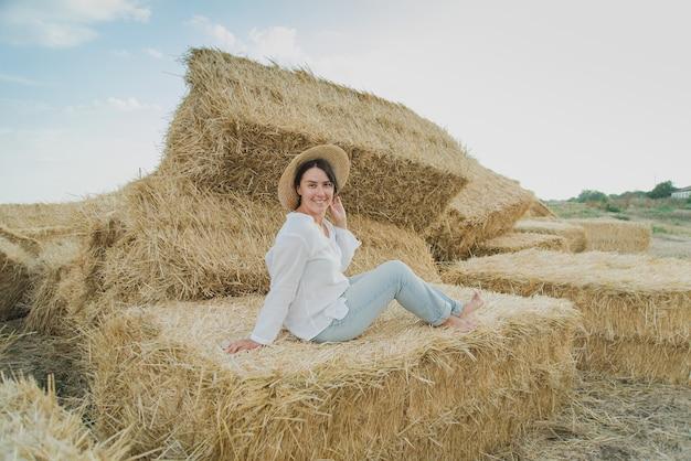 A moça veste o vestido branco do verão perto do pacote de feno no campo. Foto Premium