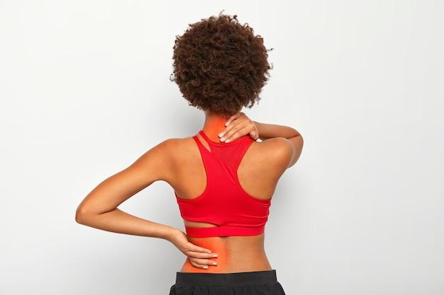 A modelo feminina morena tem dores nas articulações das costas e pescoço, tem problemas de saúde, vestida com roupa ativa isolada sobre a parede branca do estúdio Foto gratuita