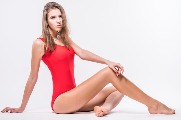 A modelo sexy com cabelo castanho está sentada no chão vestida com um maiô vermelho isolado no fundo branco Foto gratuita