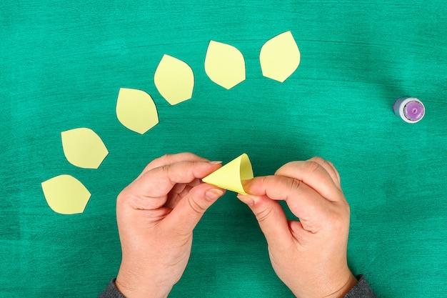 A mola de diy floresce narcisos amarelos do papel amarelo em um fundo verde. Foto Premium