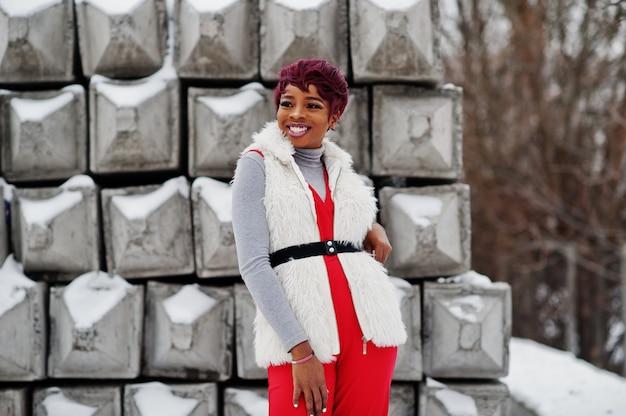 A mulher afro-americana nas calças vermelhas e no casaco branco do casaco de pele levantou no dia de inverno contra o fundo de pedra nevado. Foto Premium