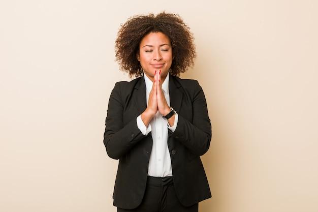 A mulher afro-americano do negócio novo que guarda as mãos reza perto da boca, sente-se confiante. Foto Premium