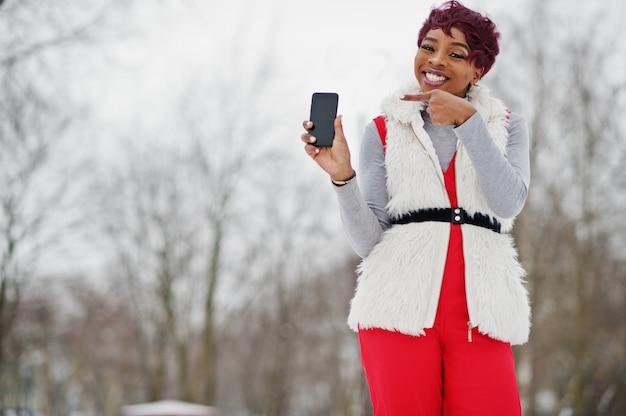 A mulher afro-americano nas calças vermelhas e no casaco branco do casaco de pele levantados no dia de inverno contra o fundo nevado, mostra o dedo para telefonar. Foto Premium