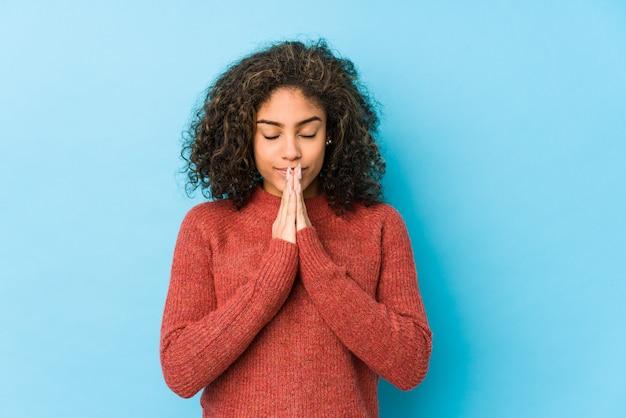 A mulher afro-americano nova do cabelo encaracolado que guarda as mãos reza perto da boca, sente-se confiante. Foto Premium