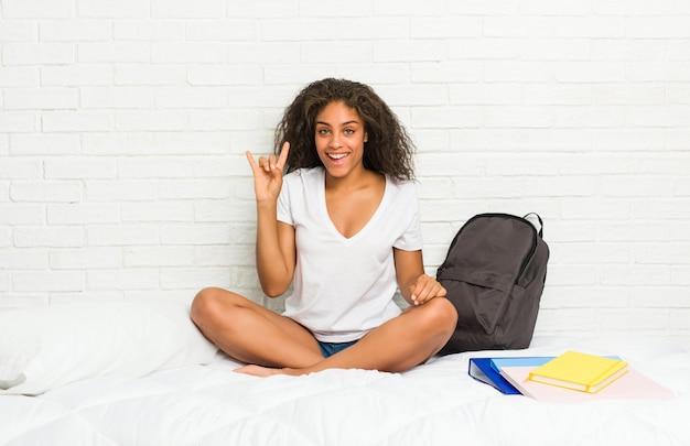 A mulher afro-americano nova do estudante na cama mostrando os chifres gesticula como um conceito da revolução. Foto Premium