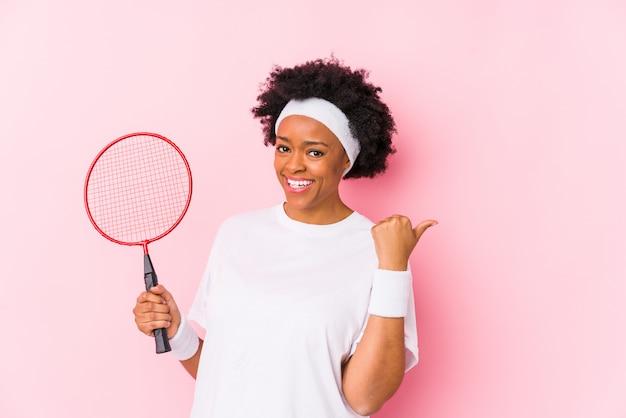 A mulher afro-americano nova que joga o badminton isolou pontos com o dedo do polegar afastado, rindo e despreocupado. Foto Premium