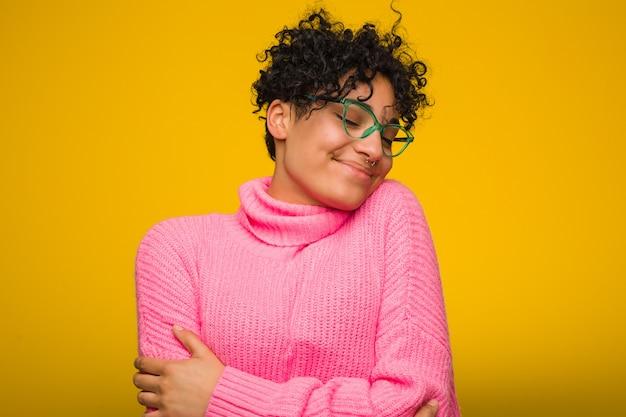 A mulher afro-americano nova que veste uma camisola cor-de-rosa abraça, sorrindo despreocupado e feliz. Foto Premium