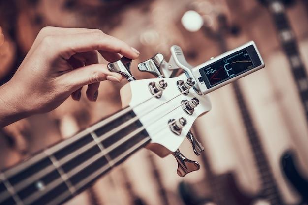 A mulher ajusta a guitarra com o grampo do afinador que torce no fretboard. Foto Premium