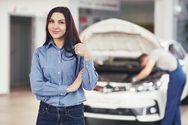 A mulher aprova o trabalho realizado pelo cliente. o mecânico trabalha sob o capô do carro Foto gratuita