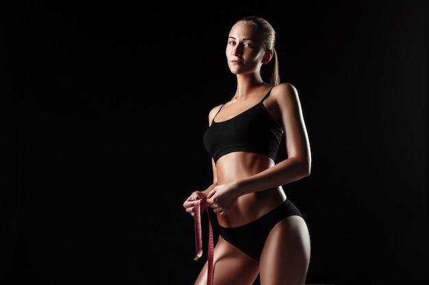 A mulher apta medindo a forma perfeita da bela figura. estilos de vida saudáveis e conceito de fitness Foto gratuita