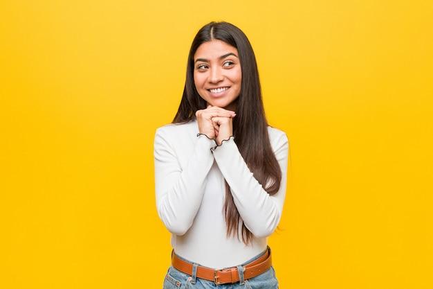 A mulher árabe bonita nova de encontro a um fundo amarelo mantem as mãos sob o queixo, está olhando feliz de lado. Foto Premium