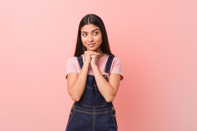 A mulher árabe consideravelmente nova que desgasta um dungaree das calças de brim mantem as mãos sob o queixo, está olhando feliz de lado. Foto Premium