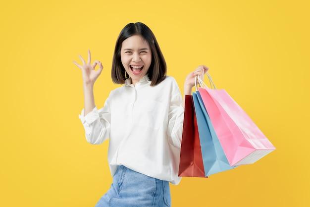 A mulher asiática bonita alegre que guarda multi sacos de compras e mostras coloridos assina o sinal aprovado. Foto Premium