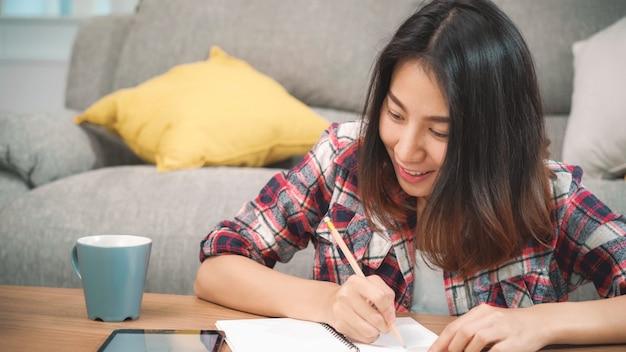 A mulher asiática do estudante faz trabalhos de casa em casa, tabuleta de utilização fêmea para procurarar no sofá na sala de visitas em casa. as mulheres do estilo de vida relaxam em casa o conceito. Foto gratuita