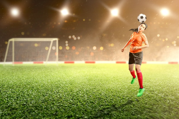 A mulher asiática do jogador de futebol salta e dirige a bola no ar no campo de futebol Foto Premium