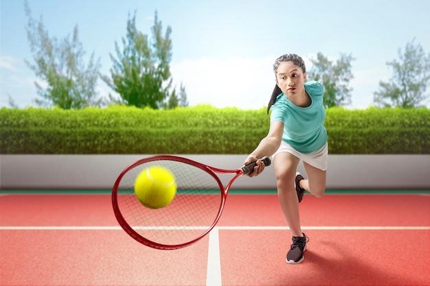 A mulher asiática do jogador de tênis balança a raquete de tênis suas mãos e joga o tênis Foto Premium