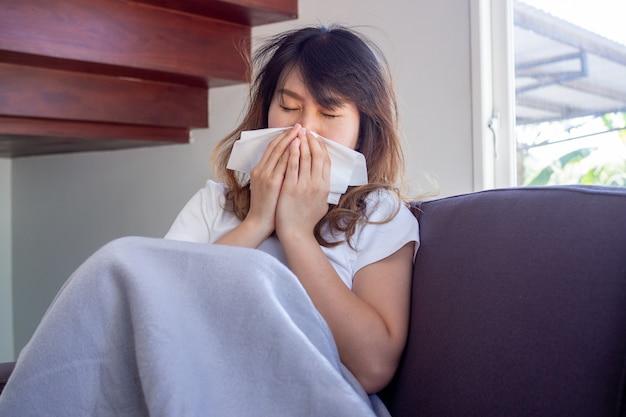 A mulher asiática estava doente no sofá da casa, com febre, tosse, espirros e nariz entupido. cobrindo o nariz com um pedaço de papel. Foto Premium