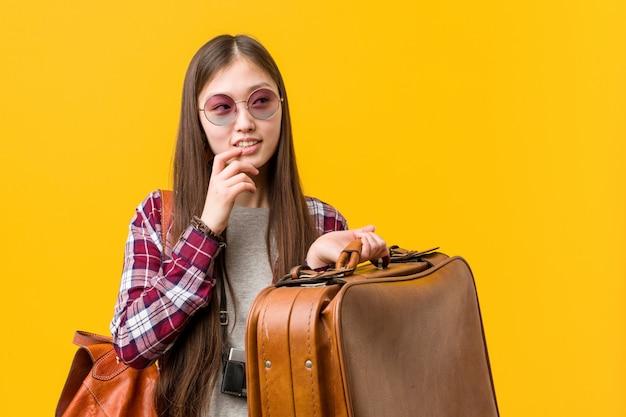 A mulher asiática nova que guarda uma mala relaxou o pensamento sobre algo que olha um espaço da cópia. Foto Premium