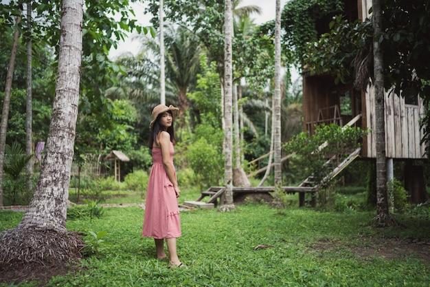A mulher asiática nova relaxa na floresta, utilização feliz fêmea bonita relaxa o tempo na natureza. Foto gratuita